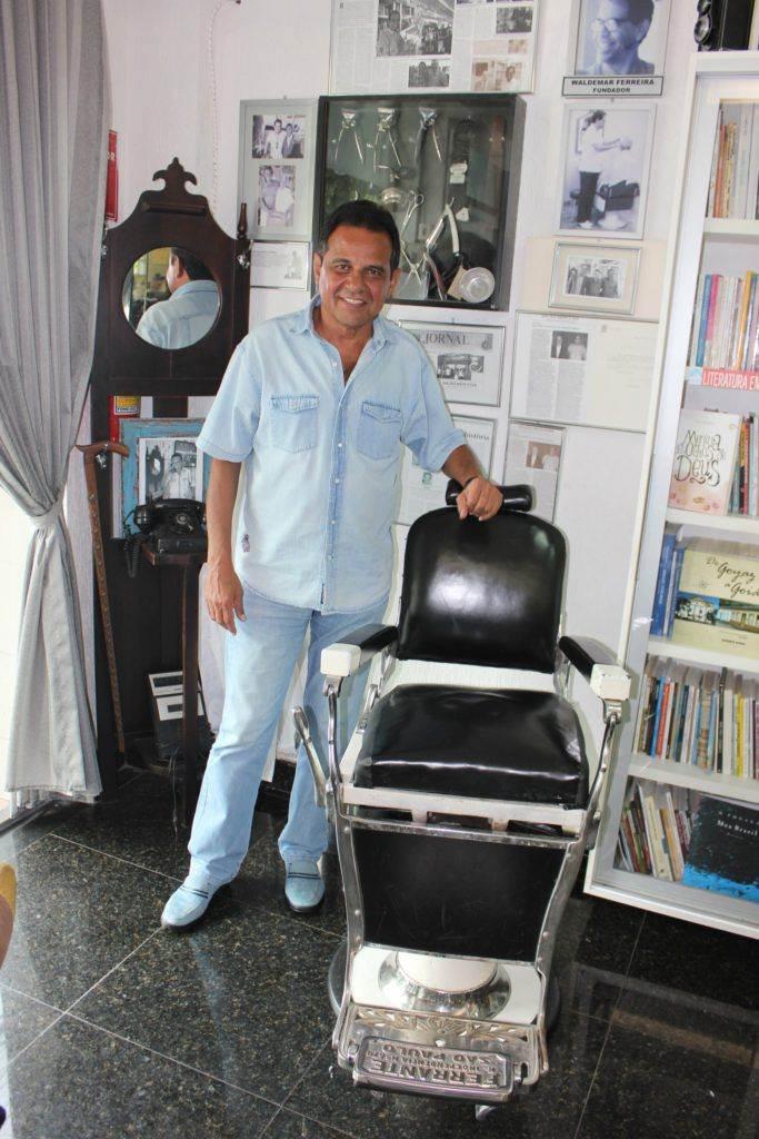 """Ruimar Ferreira posa no """"Cantinho Cultural"""" da sua barbearia, ao lado de antiga cadeira (porém conservada) herdada do pai"""